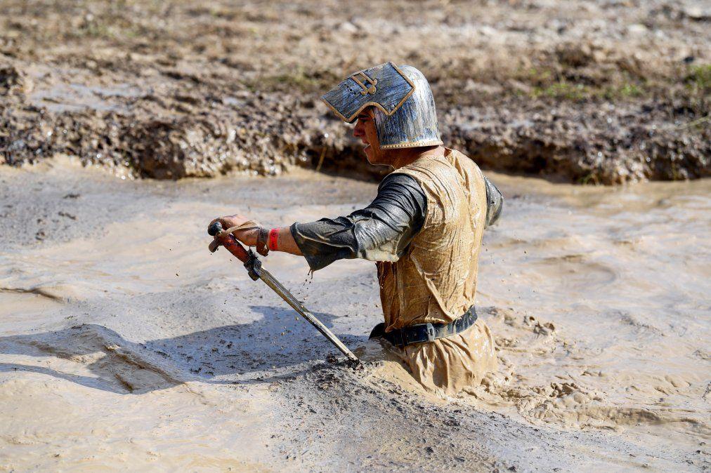 Un corredor con traje de caballero medieval participa en el Mud Day