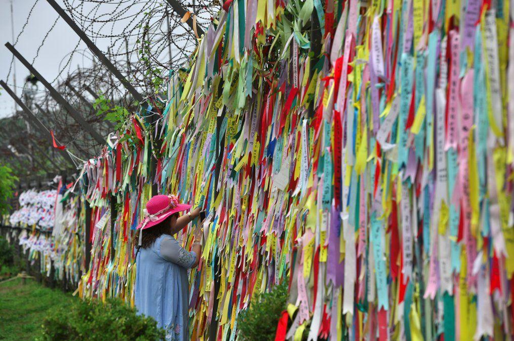 Un visitante mira cintas en pro de la paz y la reunificación de las dos Coreas en una cerca militar en el parque de paz Imjingak.