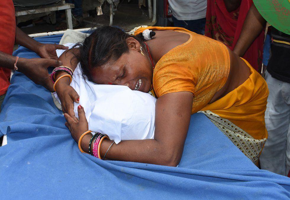 Una mujer india de duelo llora al lado del cuerpo de un bebé que murió por el llamado Síndrome de Encefalitis Aguda