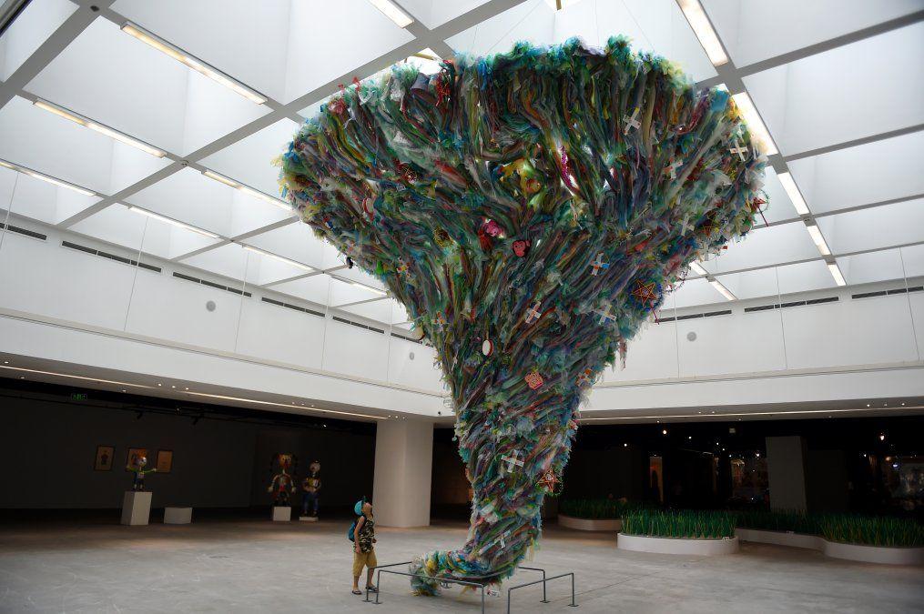 Un niño mira la instalación Tornado de basura plástica hecha por artistas en Hanoi