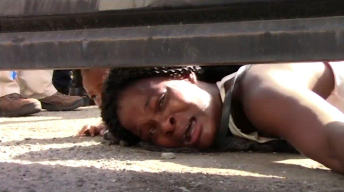 Una mujer migrante desesperada de Haití pide ayuda a los periodistas debajo de una cerca en un centro de migración de Tapachula