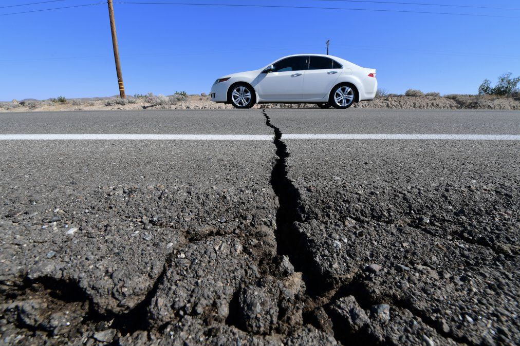Un auto pasa sobre una grieta en la Carretera 178 después de un terremoto de magnitud 6.4