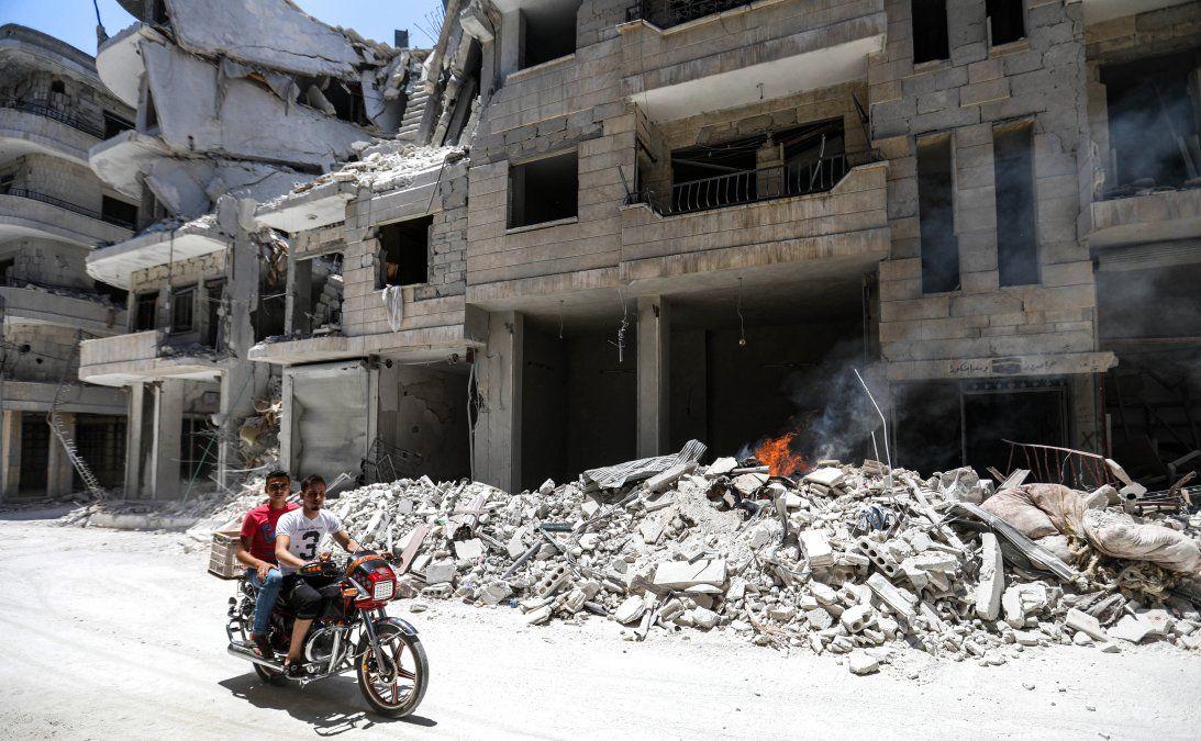 Dos hombres en moto pasan frente a un hospital destruído tras un ataque aéreo en el noroeste de Siria