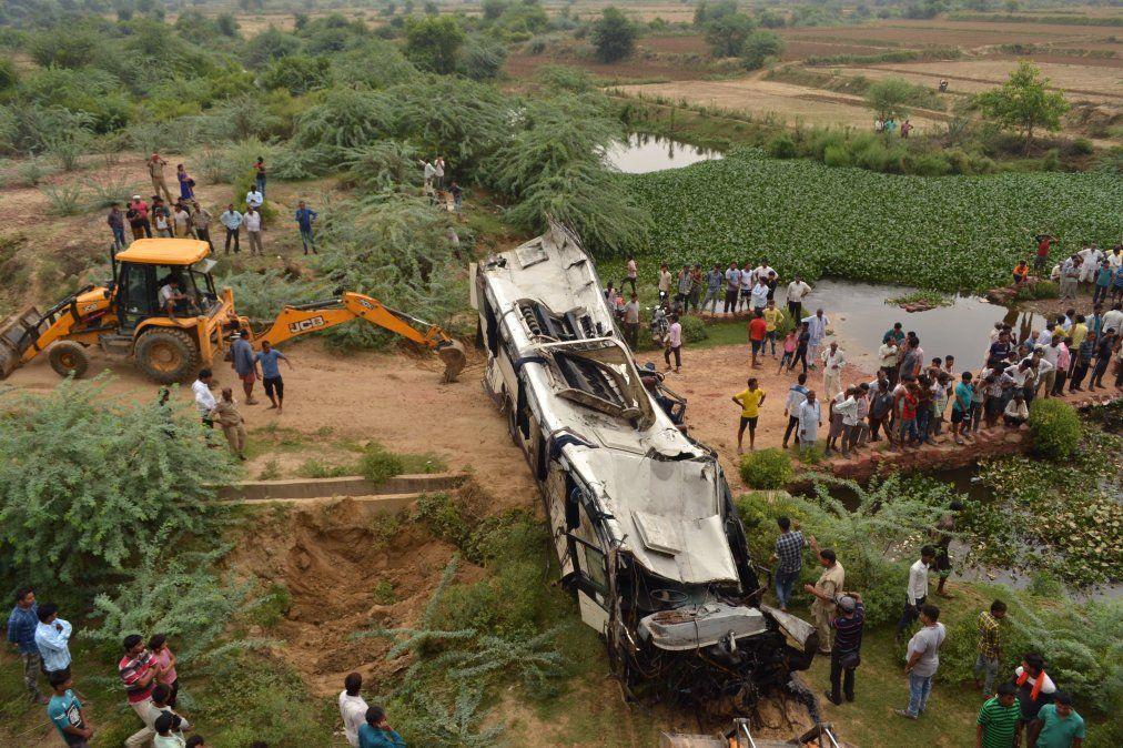 Espectadores y la Policía india se reúnen alrededor de los restos de un ómnibus que se estrelló en la autopista Delhi-Agra