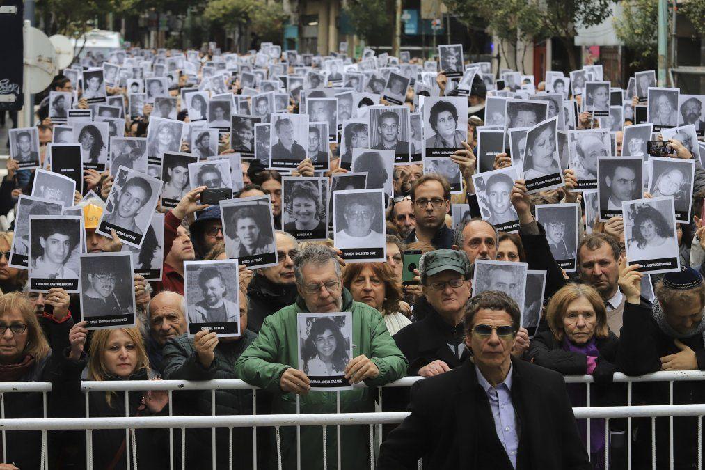 Una foto de Noticias Argentinas muestra personas sosteniendo fotos de las víctimas del atentado de la AMIA