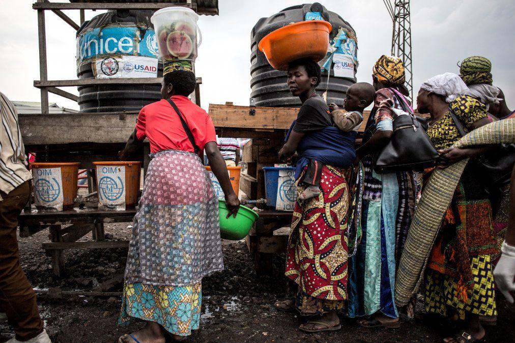 Congoleños hacen fila para lavarse las manos y tomarse la temperatura en una estación de detección de Ébola en la carretera entre Butembo y Goma