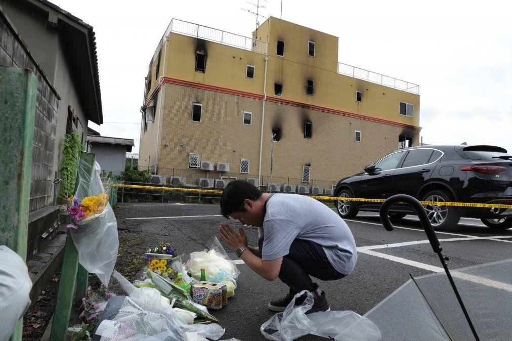 Un hombre reza junto a flores y tributos dejados en el lugar donde más de 30 personas murieron en un ataque en Japón