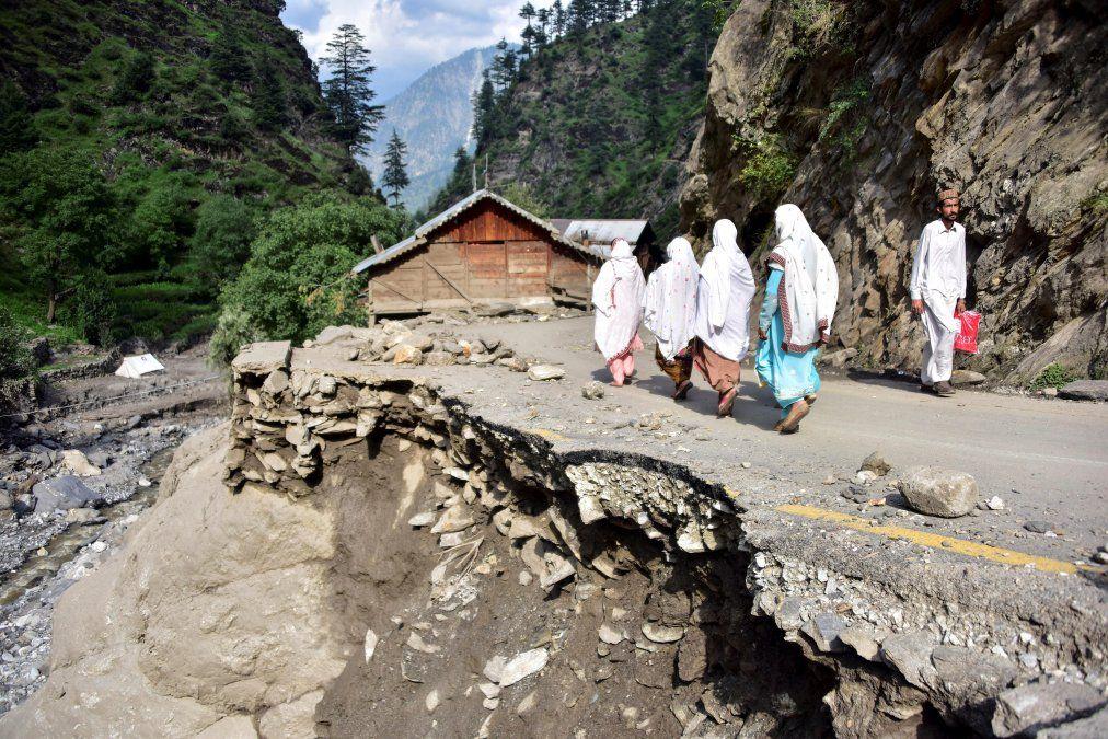 Afectados por las inundaciones en Pakistán caminan por una calle dañada en el valle de Laswa