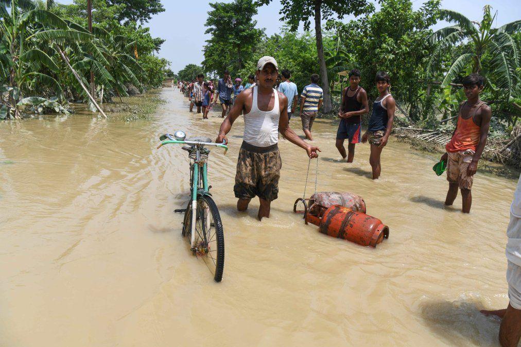 Un hombre camina por una calle inundada arrastrando su bicicleta y dos garrafas tras las fuertes lluvias monzónicas en India.