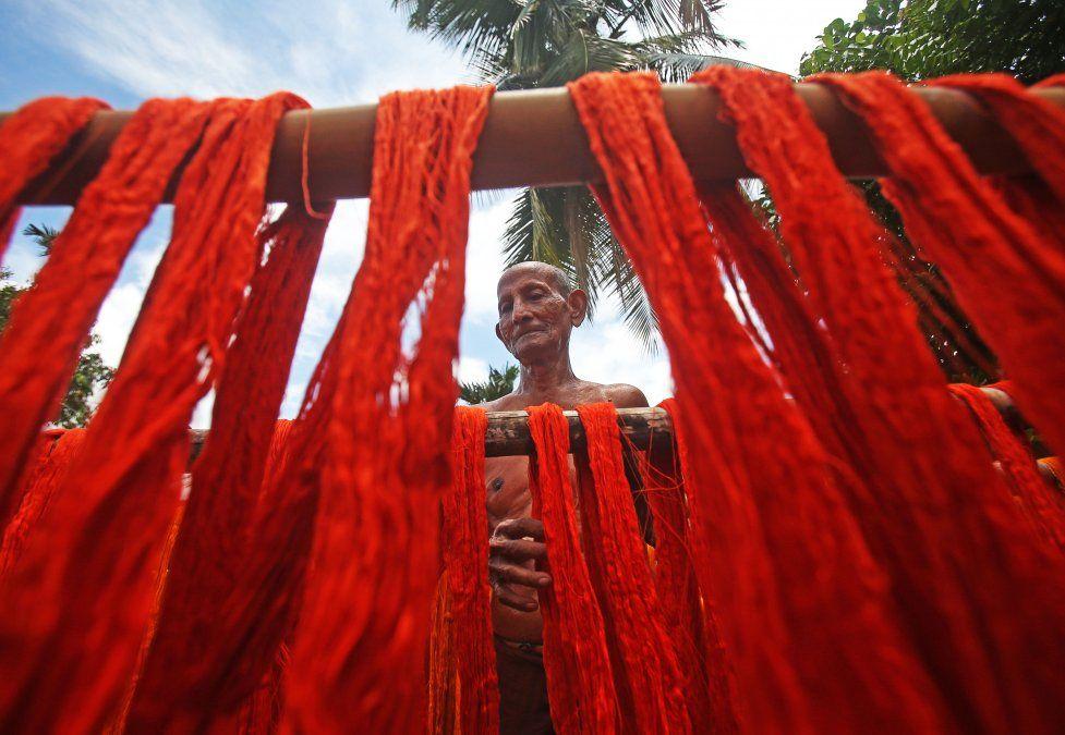 Un trabajador sostiene hilos teñidos para secar en una fábrica textil en las afueras de Agartala