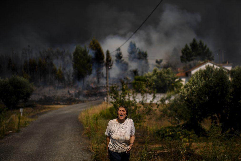 Una mujer pide ayuda a grutos mientras un feroz incendio se acerca una vivienda en la villa Casas Da Riveira