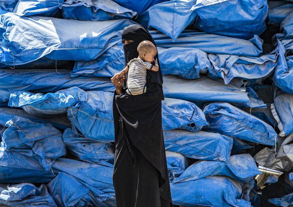 Una mujer usando un nicab camina con un bebé en el campo para desplazados en el noreste de Siria