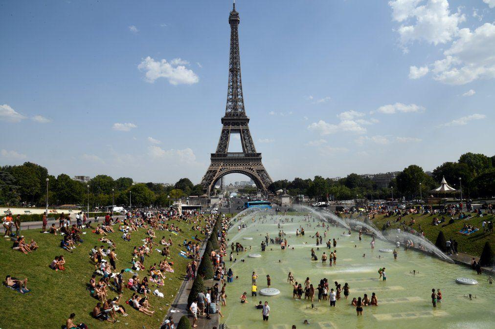 La gente se refresca y toma sol en la fuente Tricadero cerca de la Torre Eiffel en medio de la ola de calor que afecta a Europa