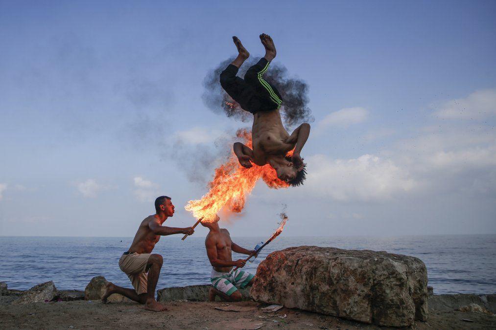 Un hombre palestino hace una performance con fuego en la playa como entretenimiento para los niños en Gaza