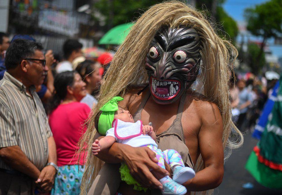Un hombre con una máscara de un personaje mitológico sosteniendo un bebé participa de un desfile en el Festival Divino Salvador del Mundo