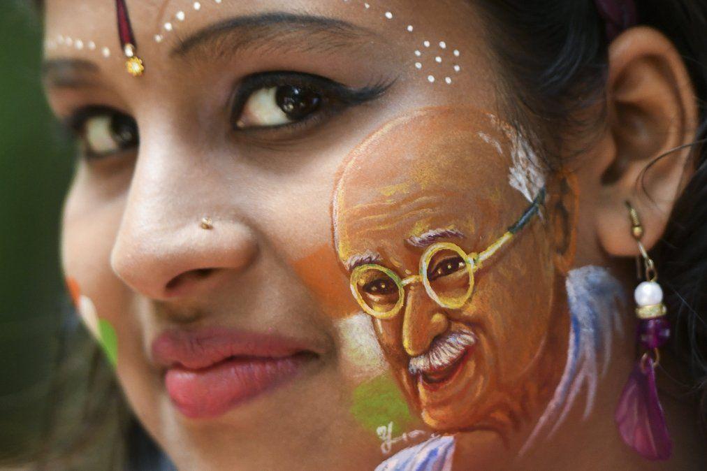 Una mujer posa con su cara pintada con un retrato de Mahatma Gandhi