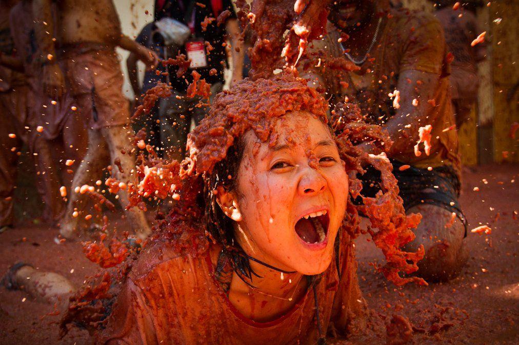 Una mujer cubierta en pulpa de tomate participa de la fiesta anual de la Tomatina