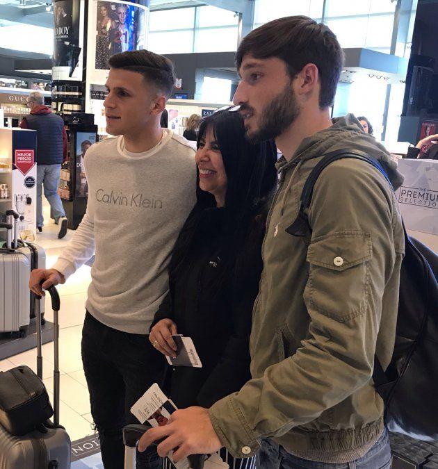 Matías Viña y Giovanni González posan con una hincha en el Aeropuerto de Carrasco.