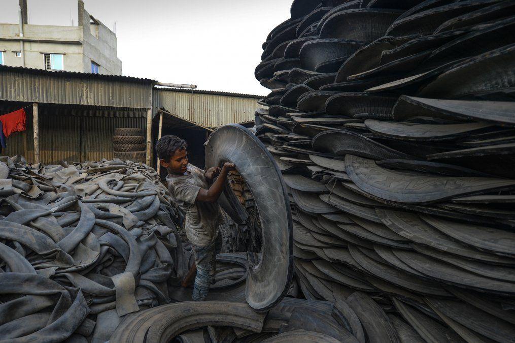 Un niño maneja piezas de una llanta vieja en Daka.