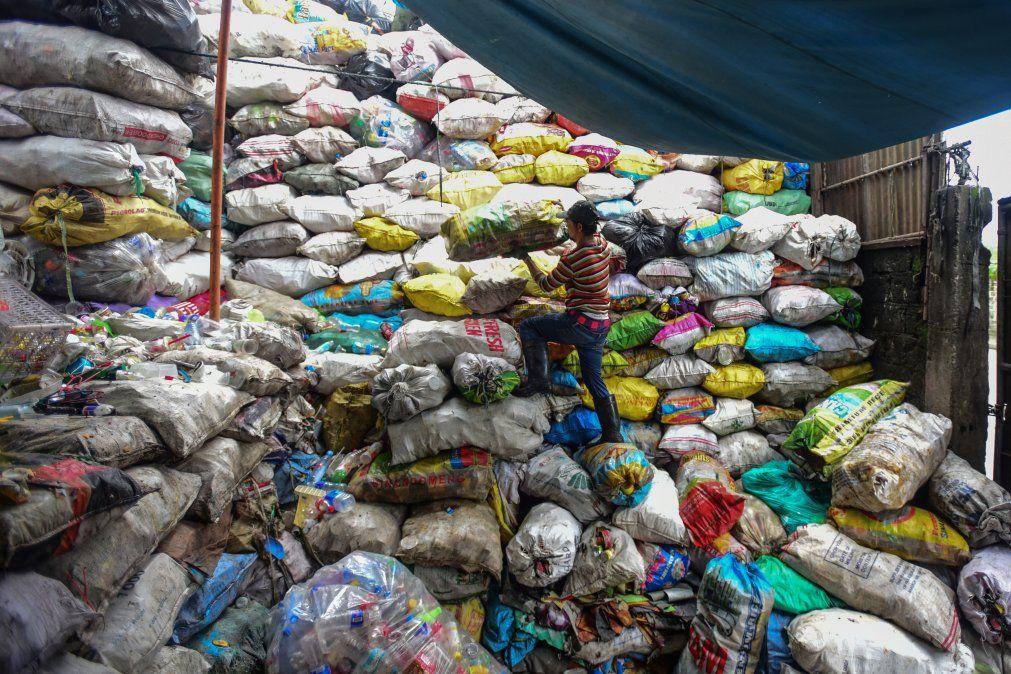 Un hombre apila bolsas de objetos plásticos de basura para ser vendidos en tiendas de reciclaje de Manila.