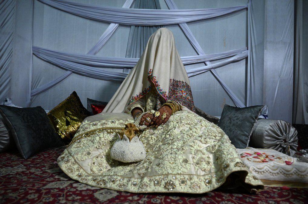 Una novia con su cara y cuerpo cubierto por con un chal se sienta en la casa de su flamante esposo tras casarse en Cachemira