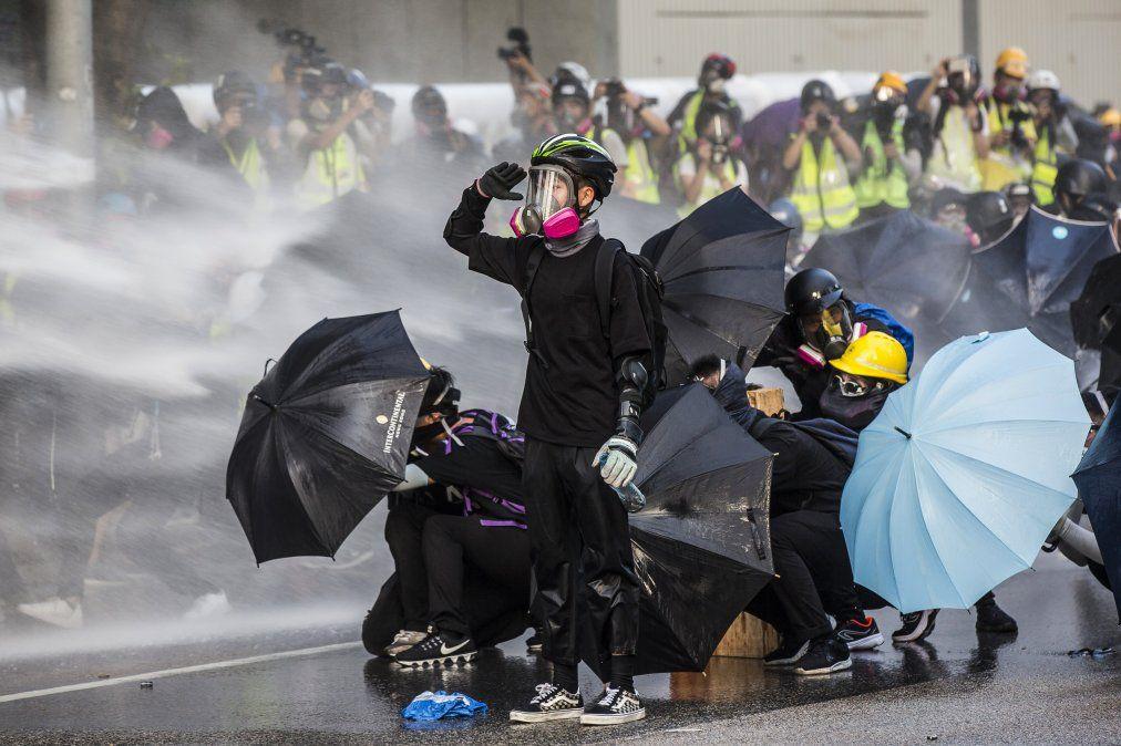 Manifestantes pro democracia reaccionan cuando la policía dispara cañones de agua fuera de la sede del gobierno de Hong Kong.