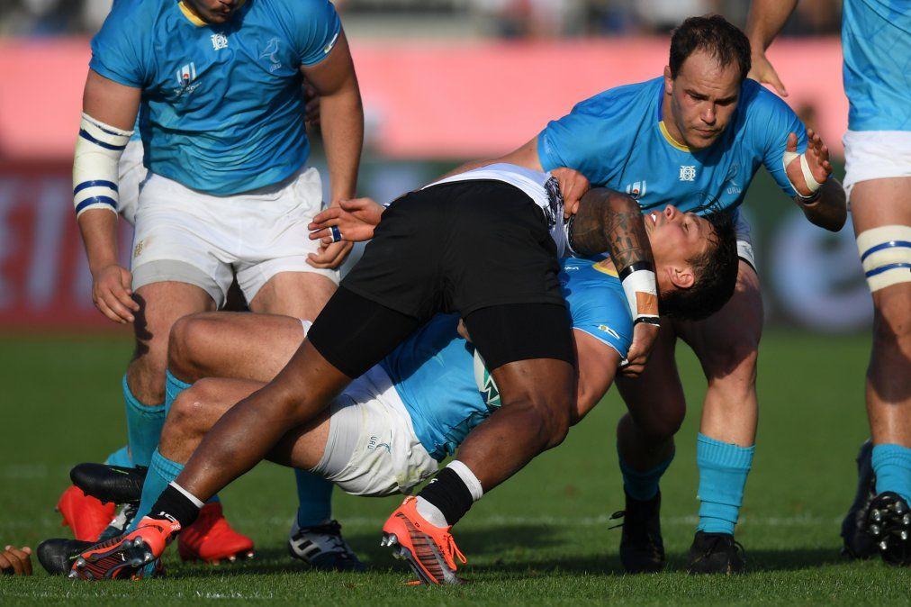 El ala uruguaya Nicolas Freitas (2R) es abordado por el medio scrum de Fiji Nikola Matawalu (C) durante el Mundial de Rugby de Japón 2019.