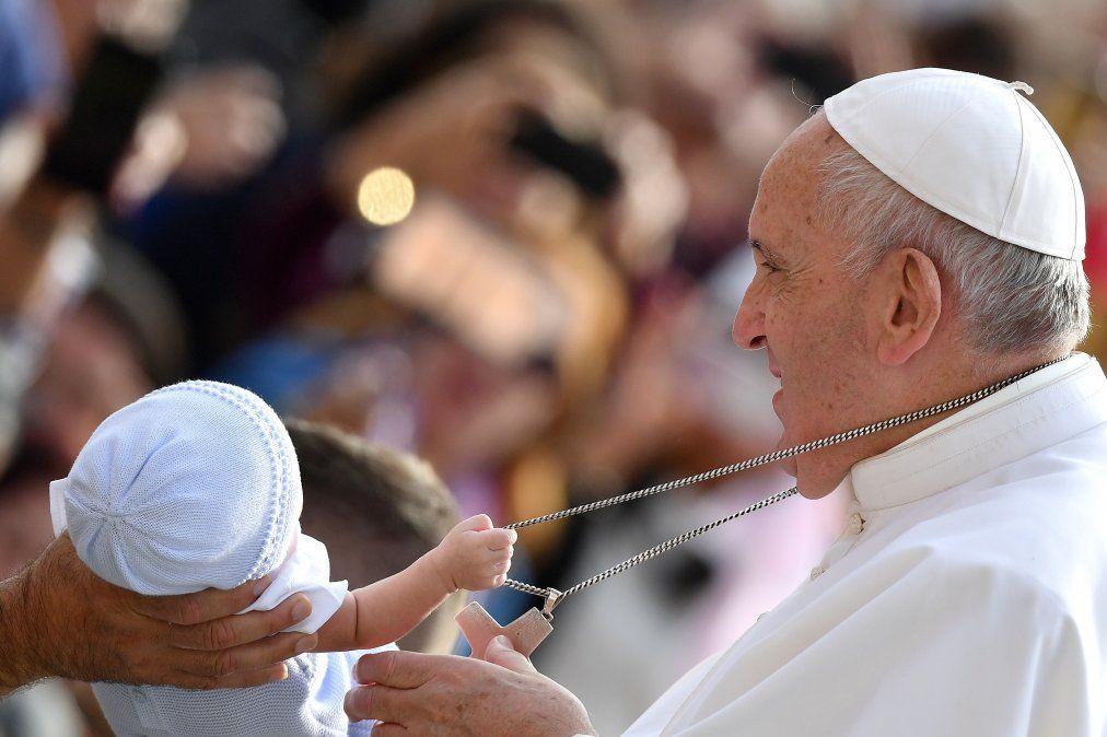Un niño tira de la cadena que cuelga alrededor del cuello del Papa Francisco mientras saluda a los fieles