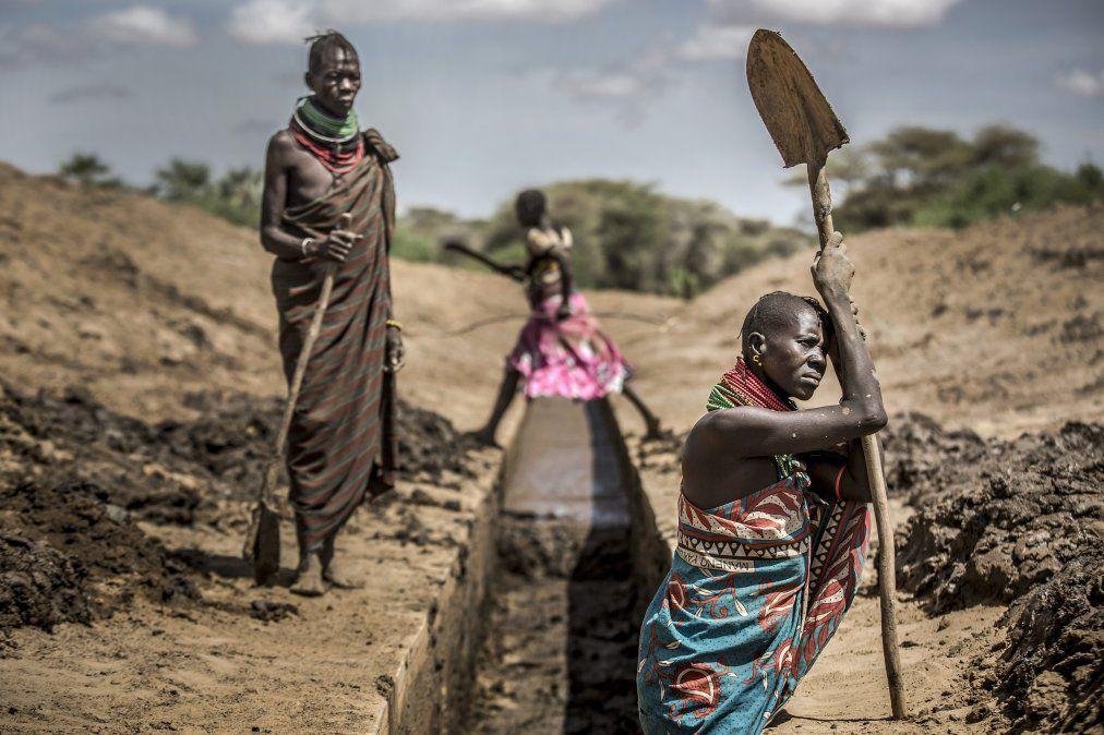 Los miembros de la comunidad de Turkana trabajan para desbloquear un canal de riego para proporcionar agua a sus cultivos de sorgo en un área árida y seca en Nanyee.