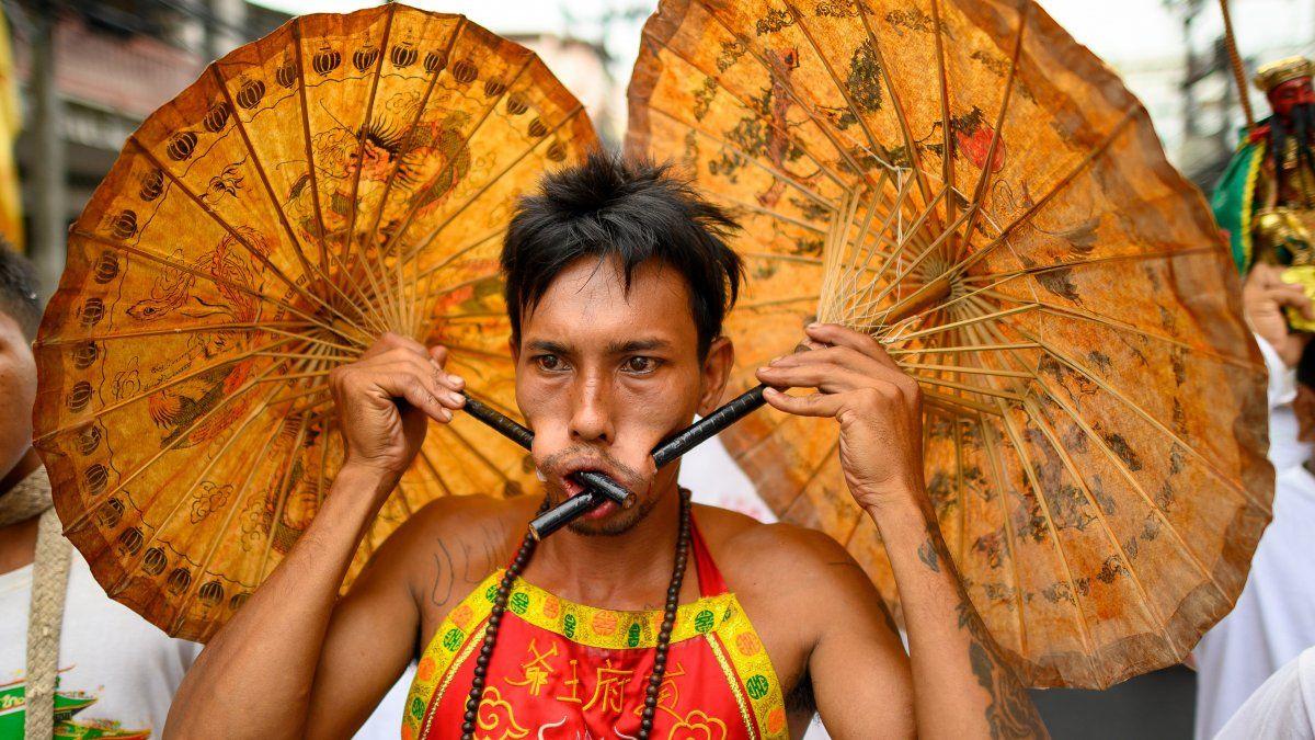 Un devoto de un santuario chino con dos paraguas perforados en sus mejillas participa en una procesión durante el Festival Vegetariano anual en Phuket.