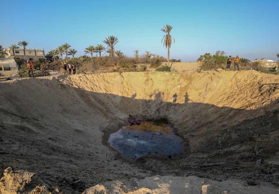 Hombres palestinos caminan alrededor de un cráter causado por un ataque aéreo israelí en respuesta al lanzamiento de cohetes en la Franja de Gaza