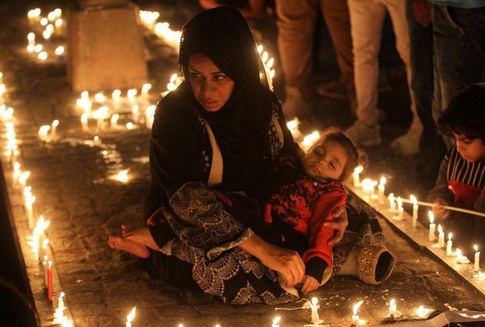 Protestante iraquí sostiene una vela en vigilia por las víctimas asesinadas durante las manifestacioes antigubernamentales en Bagdad.