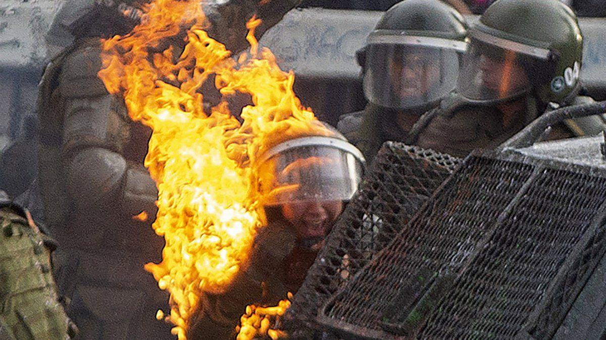 Una bomba molotov alcanza a la policía antidisturbios durante los enfrentamientos con manifestantes contra las políticas económicas de Piñera.