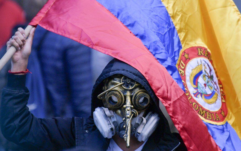 Un manifestante enmascarado flamea una bandera nacional colombiana durante una huelga nacional en Bogotá.