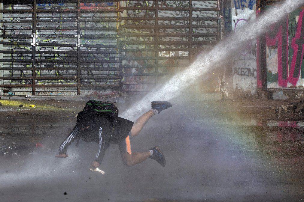 Un manifestante es alcanzado por el agua de un cañón durante una protesta contra el gobierno en Santiago de Chile.