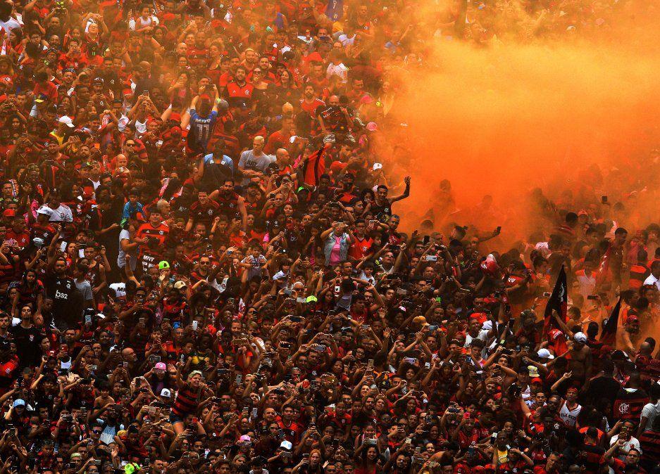 Hinchas del brasileño Flamengo saludan al equipo durante un desfile de celebración por la final de la Copa Libertadores donde el equipo le ganó a River Plate.