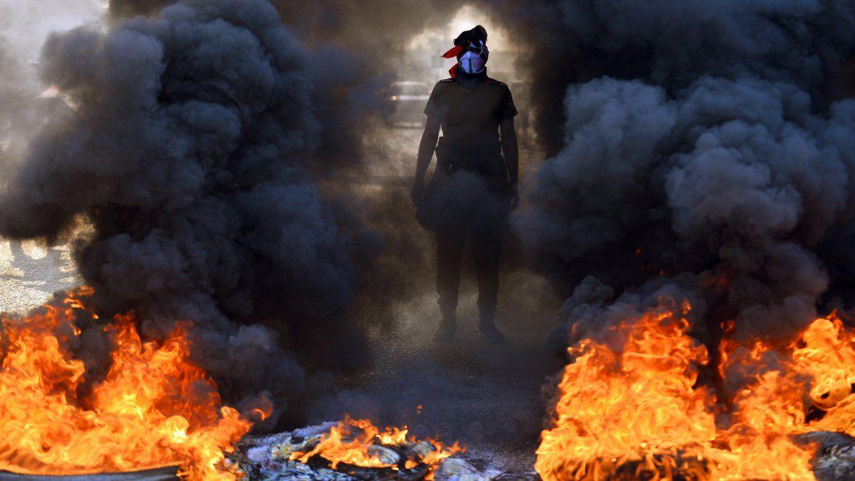 Un manifestante iraquí se para antes de quemar llantas en una barricada en la ciudad sagrada central de Najaf