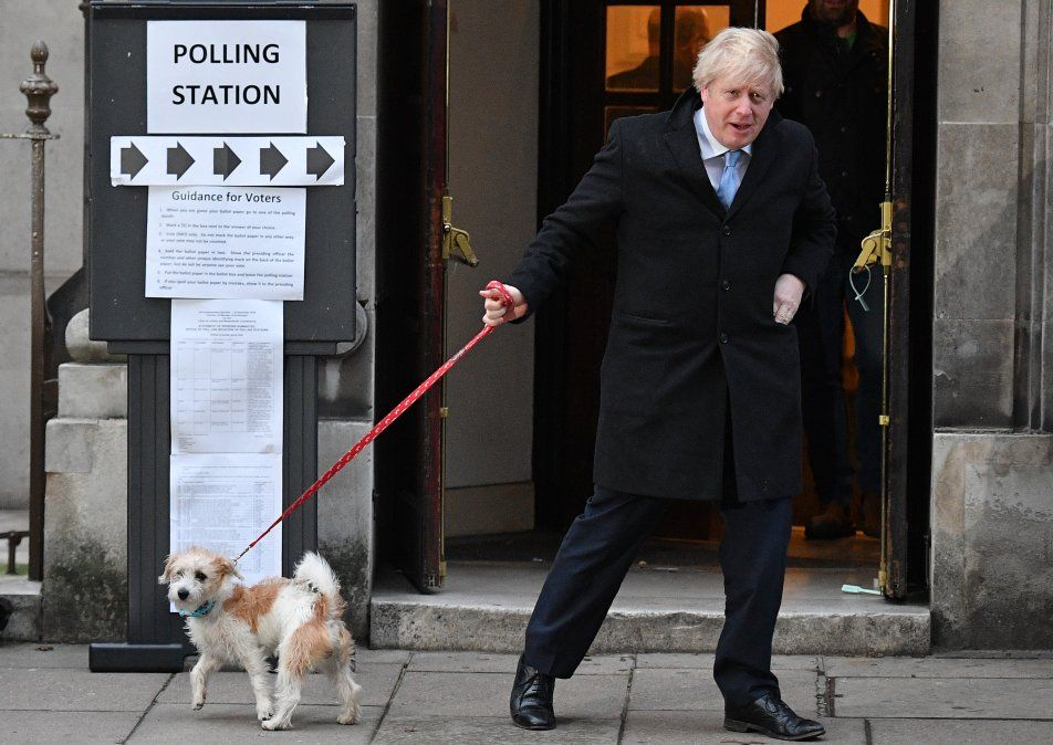El primer ministro británico Boris Johnson y su perro Dilyn se retiran de un centro de votación en el centro de Londres