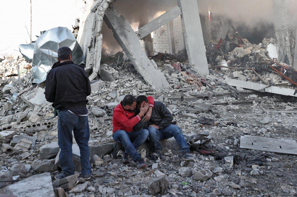 Un hombre sirio abraza a otro sobre los escombros de un edificio tras un ataque aéreo ruso en un popular mercado de Balyun