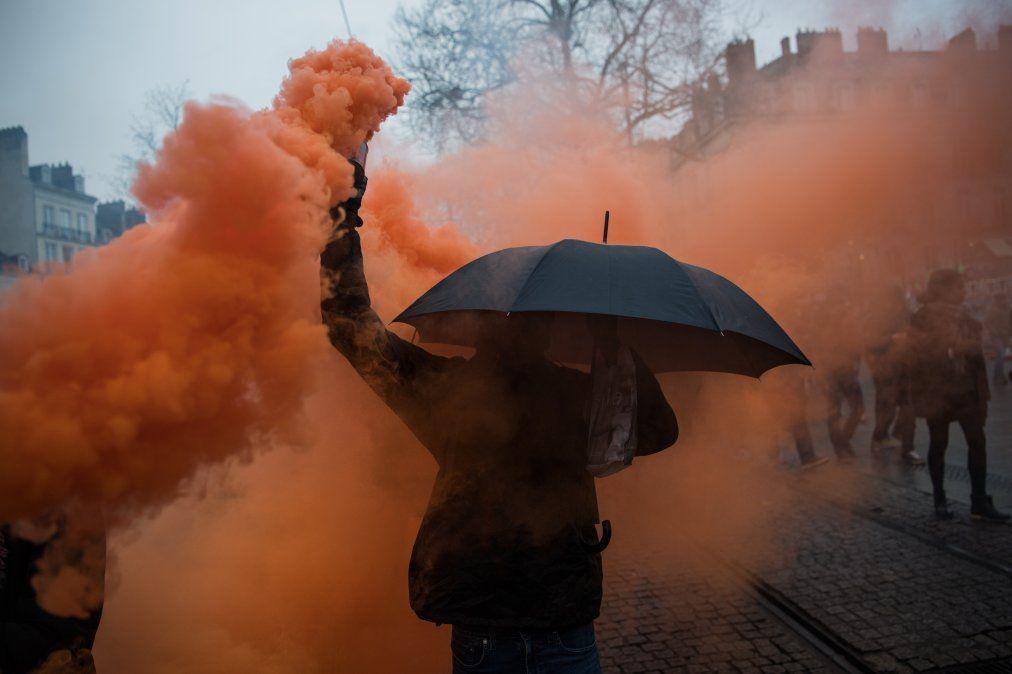 Un manifestante sostiene una lata de humo de colores durante una manifestación en Nantes