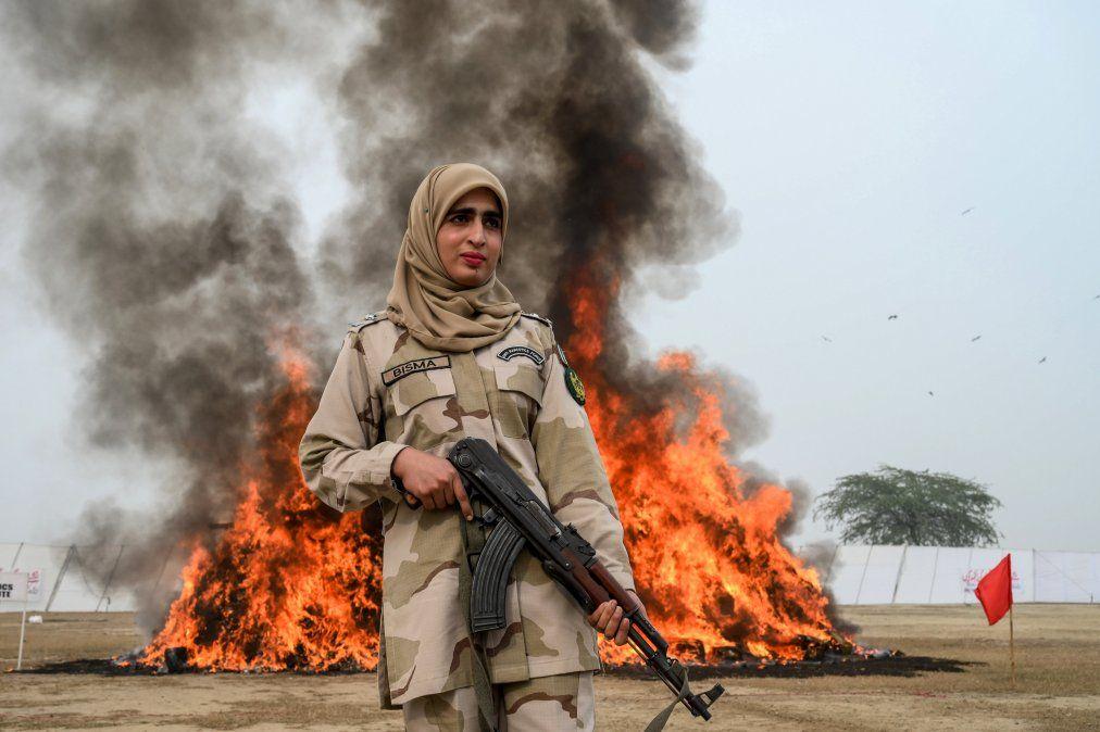 Una mujer soldado de la Fuerza Anti Narcóticos de Pakistán permanece al lado de una pila de droga incendiada