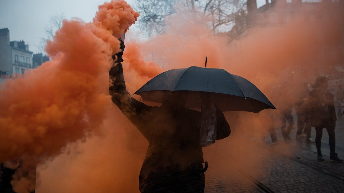 Un manifestante sostiene una lata de humo de colores durante una manifestación en Nantes, Francia, en el sexto día de huelga contra el gobierno