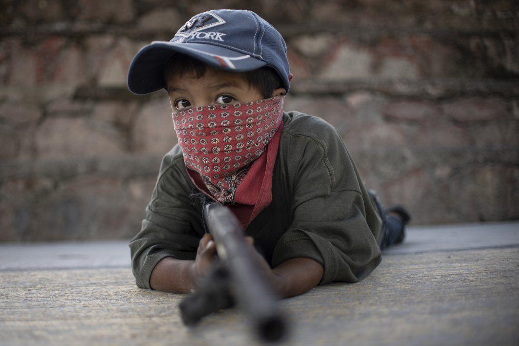 Un niño sostiene un arma improvisada donde la policía comunitaria enseña a un grupo de niños a usar armas en el estado de Guerrero.