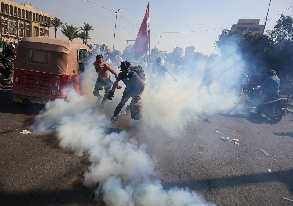 Un manifestante iraquí agarra un tubo de gas lacrimógeno disparado por la policía antidisturbios en medio de enfrentamientos tras manifestaciones antigubernamentales en Bagdad.