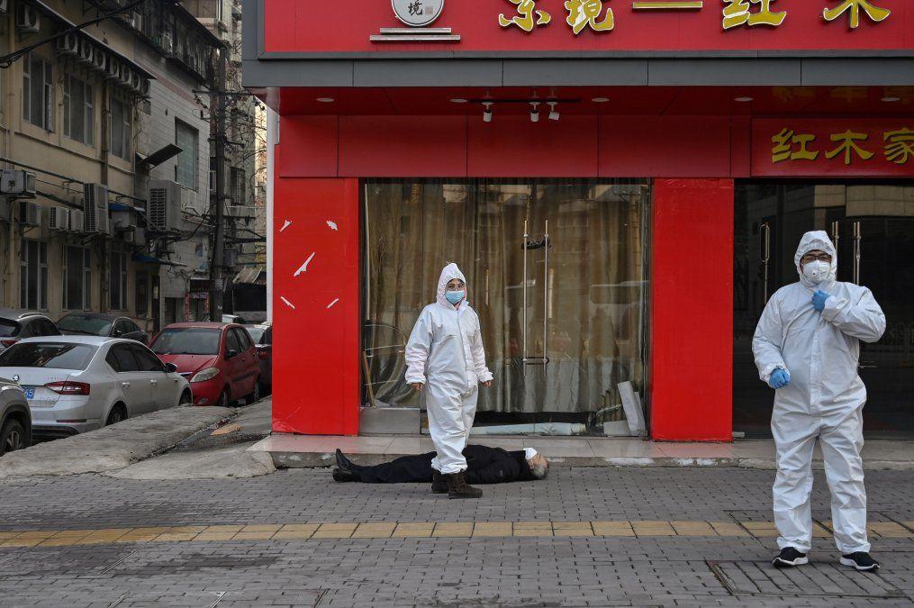 Dos médicos con trajes protectores chequean a un anciando con tapabocas que colapsó y murió en la calle ceca del hospital de Wuhan