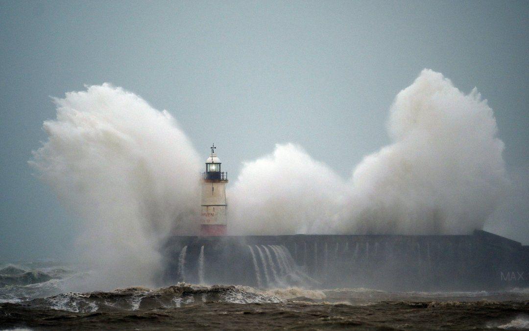 Las olas rompen sobre el faro de Newhaven en la costa sur de Inglaterra