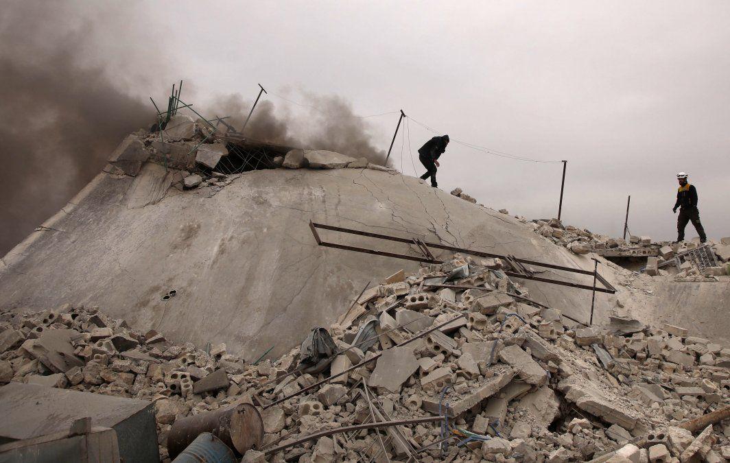 Los equipos de rescate conocidos como el Casco Blanco buscan víctimas entre los escombros de una casa que fue destruida durante un ataque aéreo de las fuerzas pro-régimen en el campo occidental de Alepo
