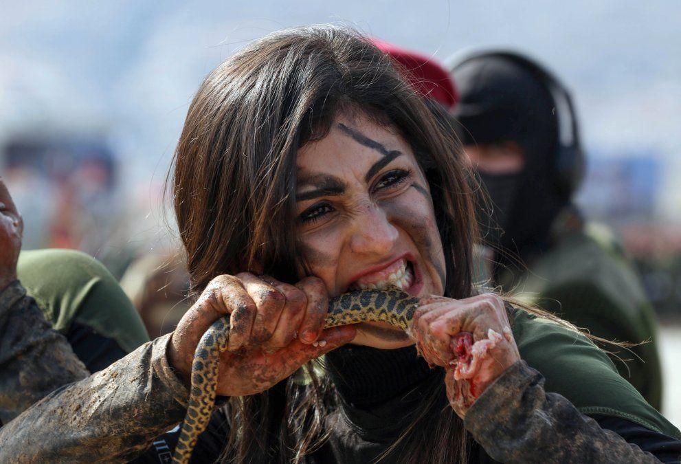 Una oficial peshmerga kurda iraquí muerde una serpiente mientras demuestra habilidades durante una ceremonia de graduación en la ciudad kurda de Soran