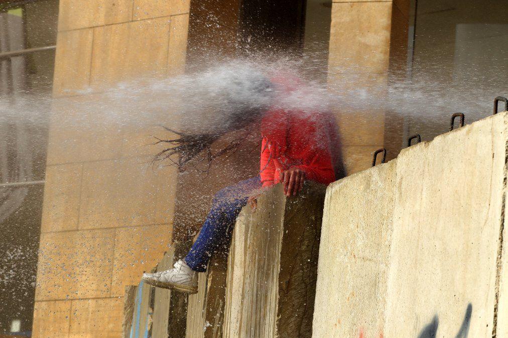 Un manifestante libanés es alcanzado por un cañón de agua durante los enfrentamientos con soldados del ejército