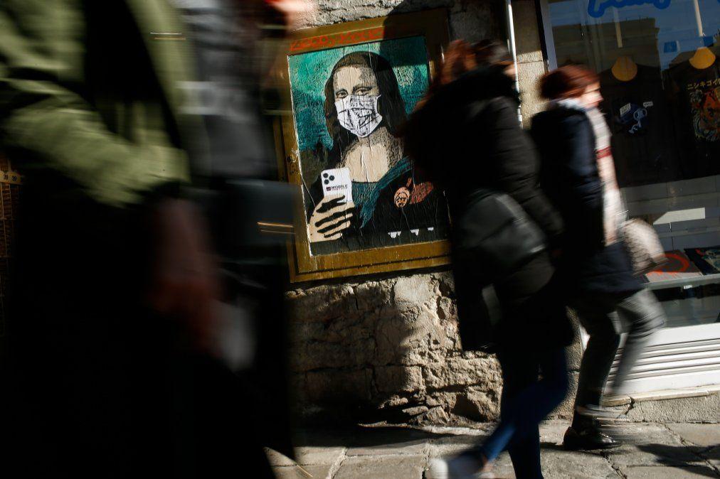 La gente camina cerca de un poster de un artista urbano italiano Salvatore Benintende que retrata a la Mona Lisa de Leonardo Da Vinci usando un tapabocas.